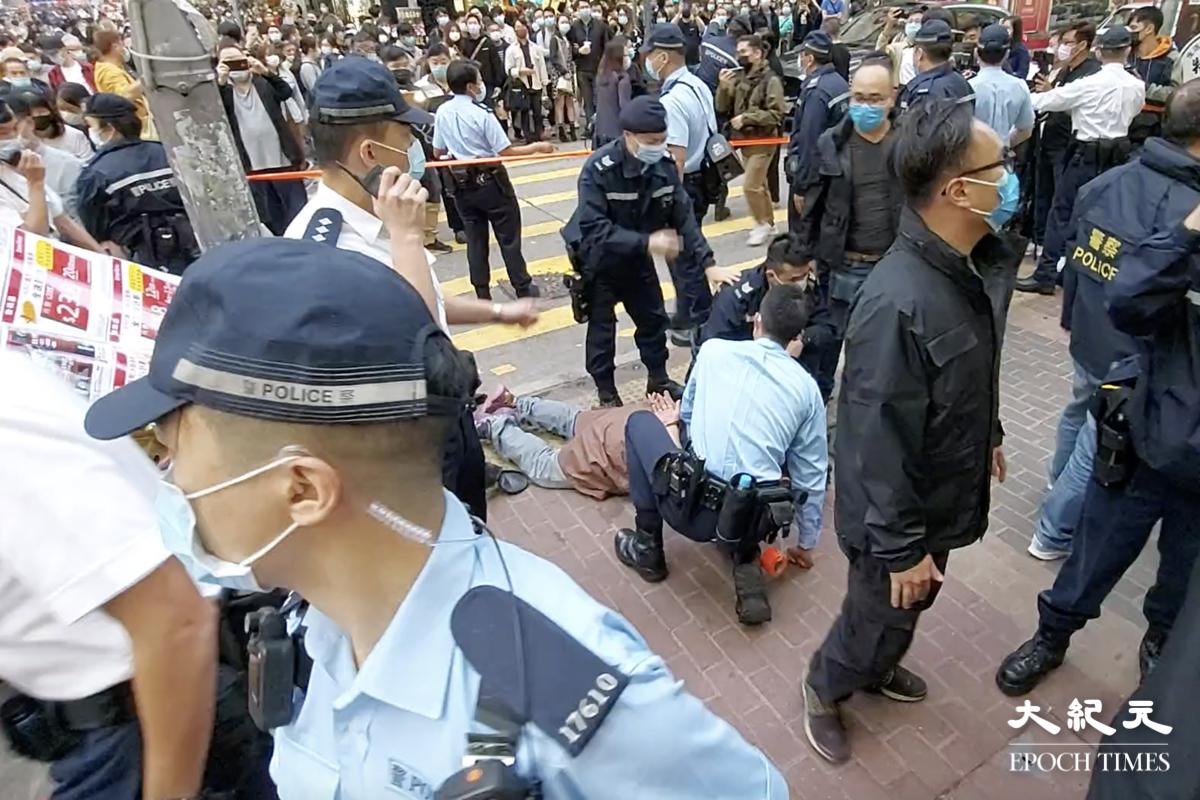 今(2月28)日下午,賢學思政及醫管局員工陣線在旺角擺放街站,被大約20名機動部隊成員突然封鎖街站。期間警方與在場人士發生口角,又將一名男子壓在地上,並將其拘捕。(麥碧/大紀元)