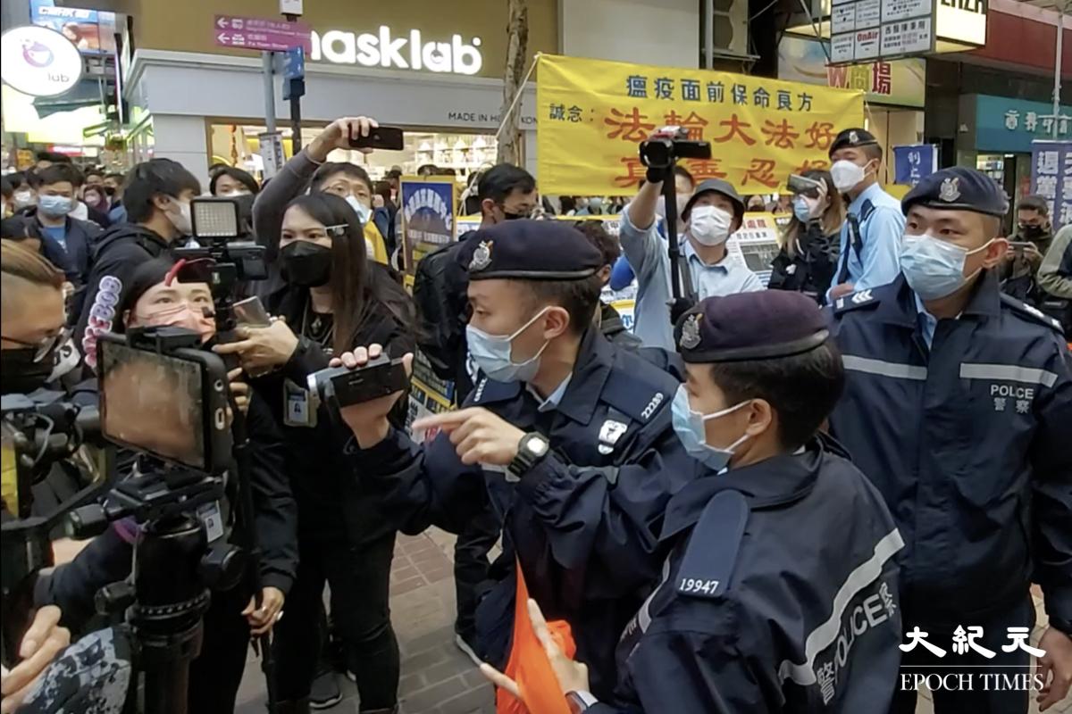 今(2月28)日下午,賢學思政及醫管局員工陣線在旺角擺放街站,被大約20名機動部隊成員突然封鎖街站。圖為警方作出拘捕前的一刻。(麥碧/大紀元)