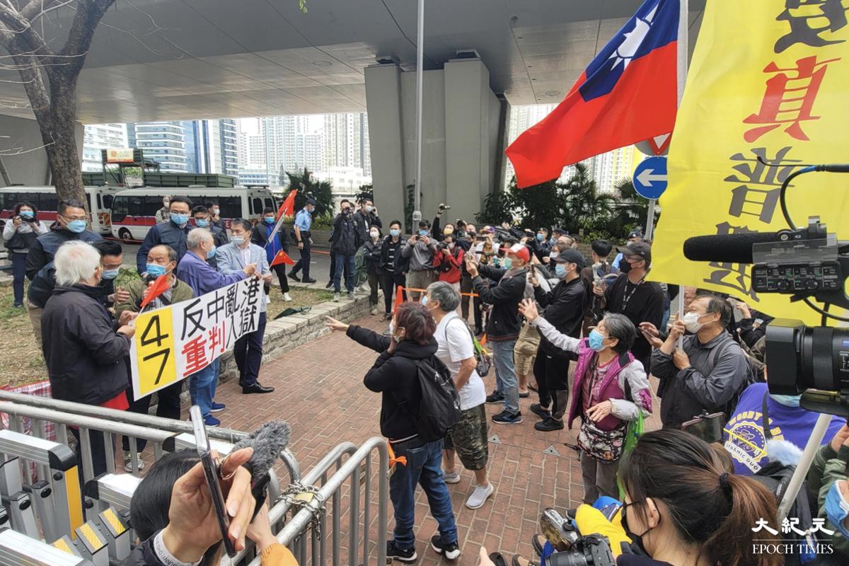 數名親政府人士手持國旗及標語,於西九龍裁判法院外圍高叫口號,警方特別拉起「橙帶」將其與支持47人的市民隔開,雙方對罵。(宵龍/大紀元)