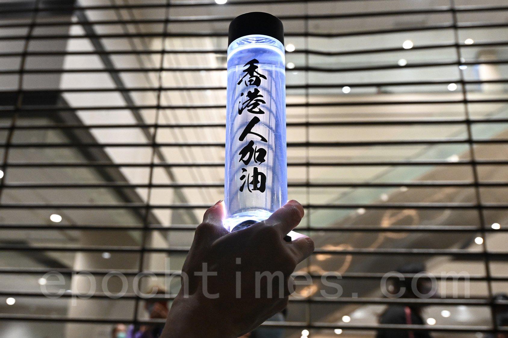 有市民高舉寫有「香港人加油」的水瓶到法庭外聲援。(宋碧龍/大紀元)