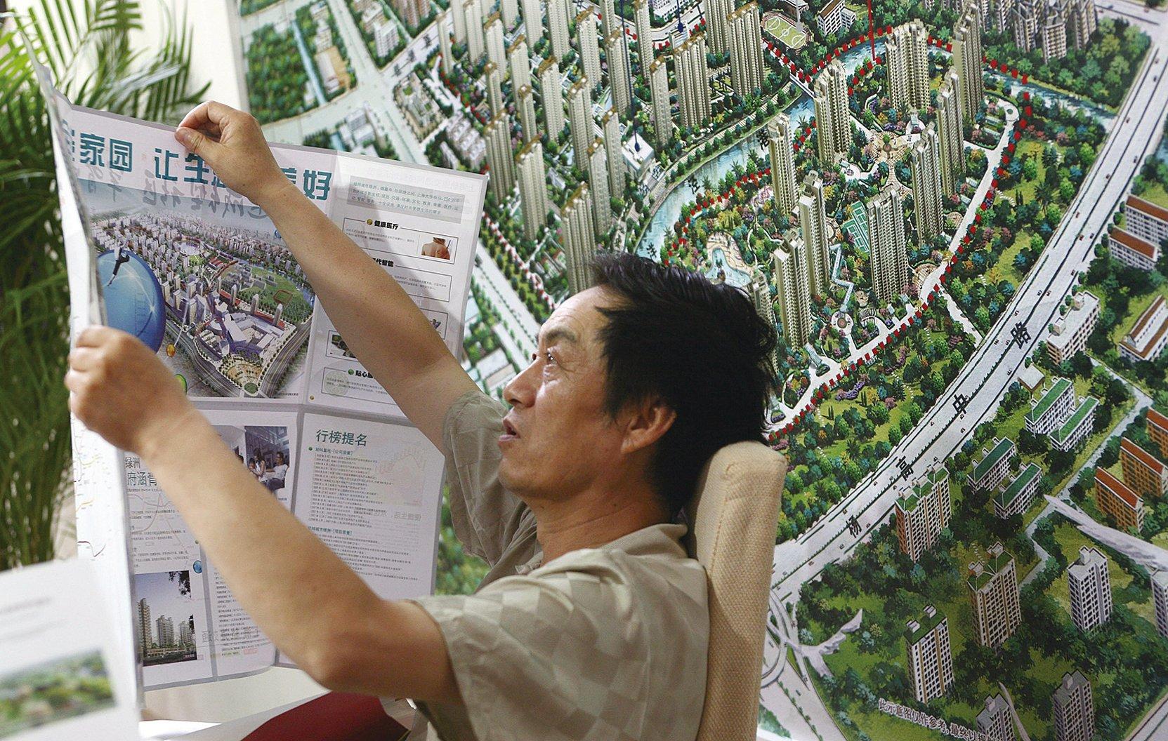 近日有消息傳,上海市將於9月份再推出收緊按揭的政策。上海市住房成交量上周再創高峰,上海房產交易中心系統一度癱瘓。當周上海新房成交量累計高達5009套。圖為一購房者正在上海某樓盤模型前閱讀房產廣告。(Getty Images)