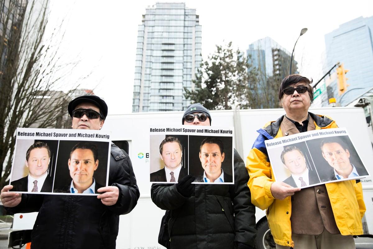 2019年3月6日孟晚舟出庭時,抗議者在法庭外舉著加拿大人邁克爾·斯帕沃爾(Michael Spavor)和邁克爾·康明凱(Michael Kovrig)的照片,抗議中共的人質外交。(Jason Redmond / AFP)