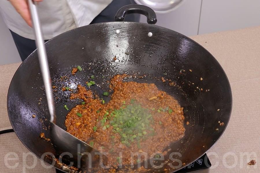將剩餘的2湯匙蔥花加入肉醬。(陳仲明/大紀元)
