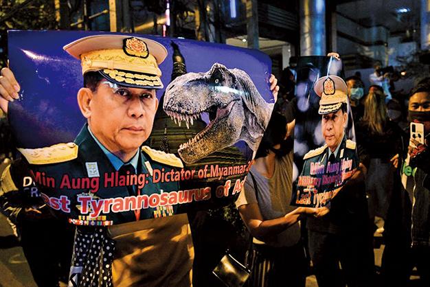 圖為一名抗議者舉著印有緬甸軍方負責人敏昂萊和一隻恐龍形象的橫幅,參加譴責軍事政變的抗議活動。(Getty Images)