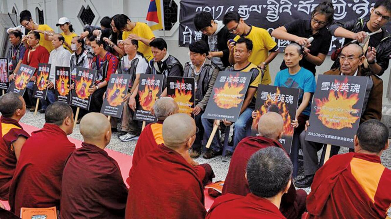 圖為2011年10月19日,在台北自由廣場前的一次抗議活動中,藏人展示了在自焚中喪生的人的畫像。(SAM YEH/AFP via Getty Images)