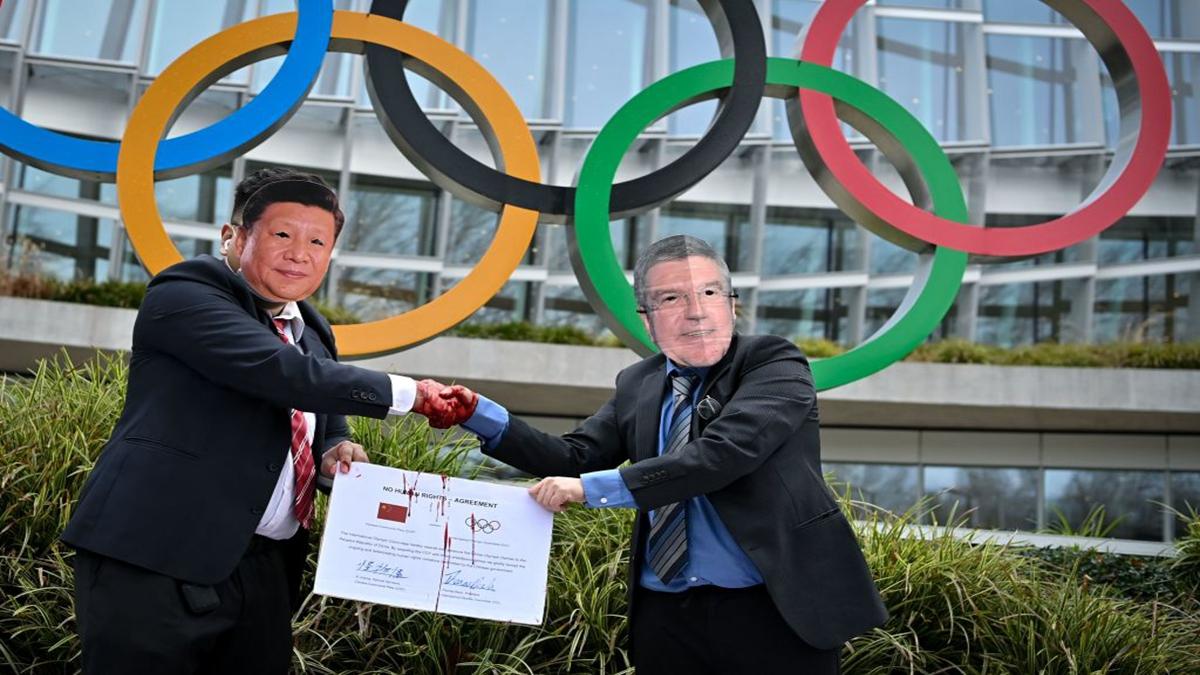 2月3日,國際西藏網絡的活動家,在抗議北京2022年冬季奧運會的活動中,戴著習近平和巴赫的面具,在國際奧委會總部前握手。( FABRICE COFFRINI/AFP )
