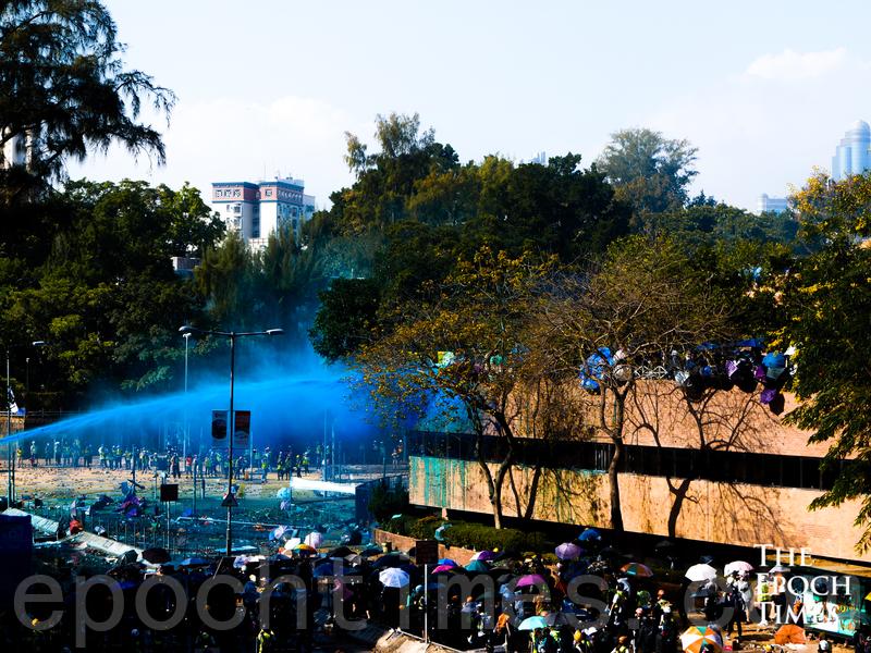 2019年11月,警方水炮車向理工大學校園內外的抗爭者發射藍水水炮。(大紀元)