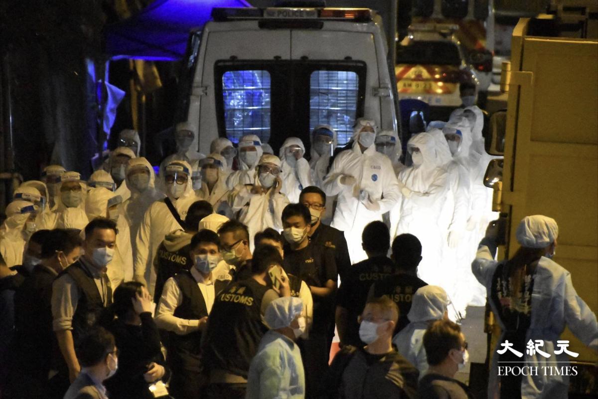 晚上9時40分,一批穿著保護衣人員在興華大廈和金鳳閣現場準備。(麥碧/大紀元)