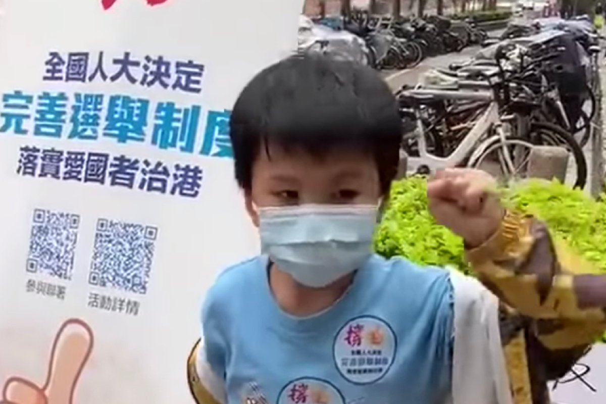 一名5-6歲兒童站在「撐人大決定完善選舉制度」的易拉架前,揮動拳頭,表示「國家要藍 不可以做黃」「黃的不是好人」。(視頻截圖)