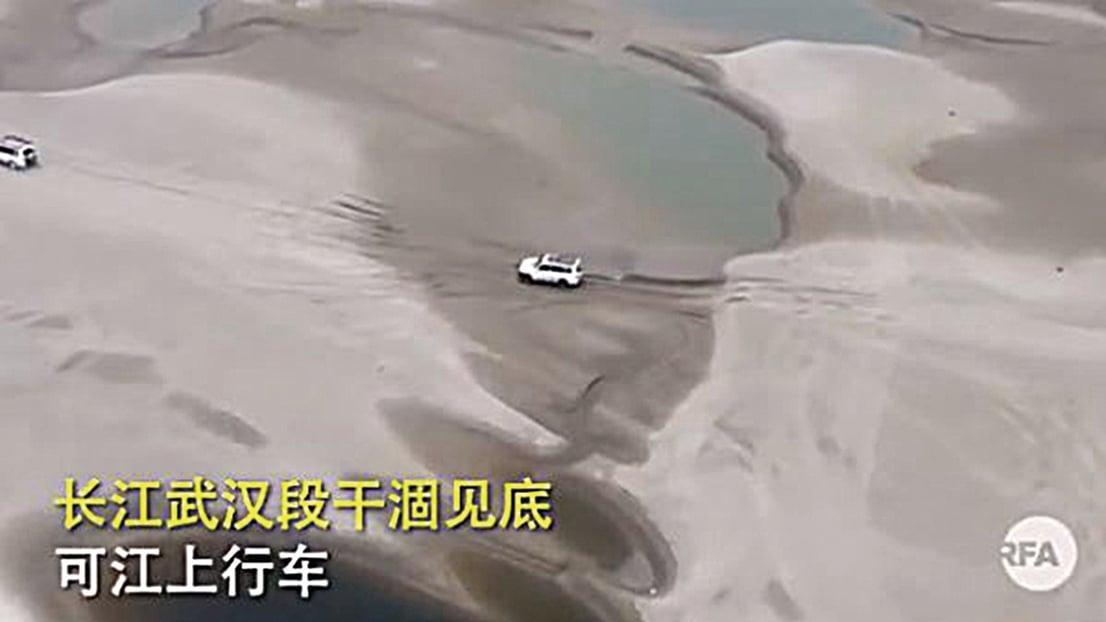 3月15日,網上傳出的影片顯示,長江武漢段已經乾涸見底,河床變成了沙灘,汽車直接在江中行駛。(影片截圖)