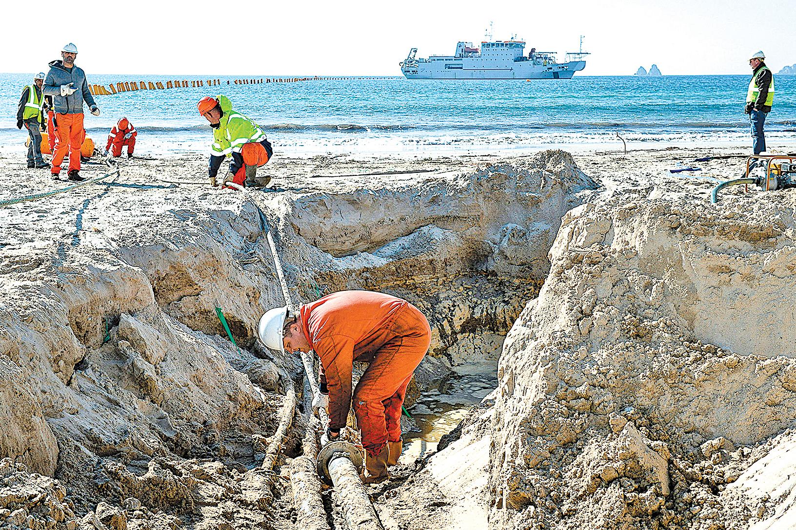 圖為2016年3月1日,工人在法國南部La Seyne-sur-Mer海灘安裝超高速海底電纜。(Getty Images)