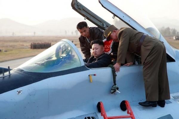 圖為北韓領導人金正恩登上空軍一架軍機駕駛座瞭解設備。(KNS / KCNA / AFP)