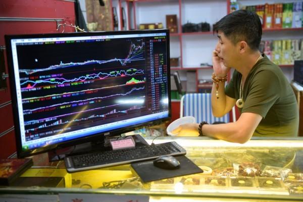 目前,各方面跡象顯示中國經濟持續惡化,但中共官方所公佈的數據能否可靠則是讓人頭疼的問題。福布斯投資專欄刊文稱,要知道中國經濟真相,就要把中共官方數據忽略,轉而去查找相鄰亞洲國家的數據才能知道真相。圖為8月15日,上海一名商戶在打電話,而他旁邊的屏幕則在顯示中國股市走向。(PETER PARKS/AFP/Getty Images)