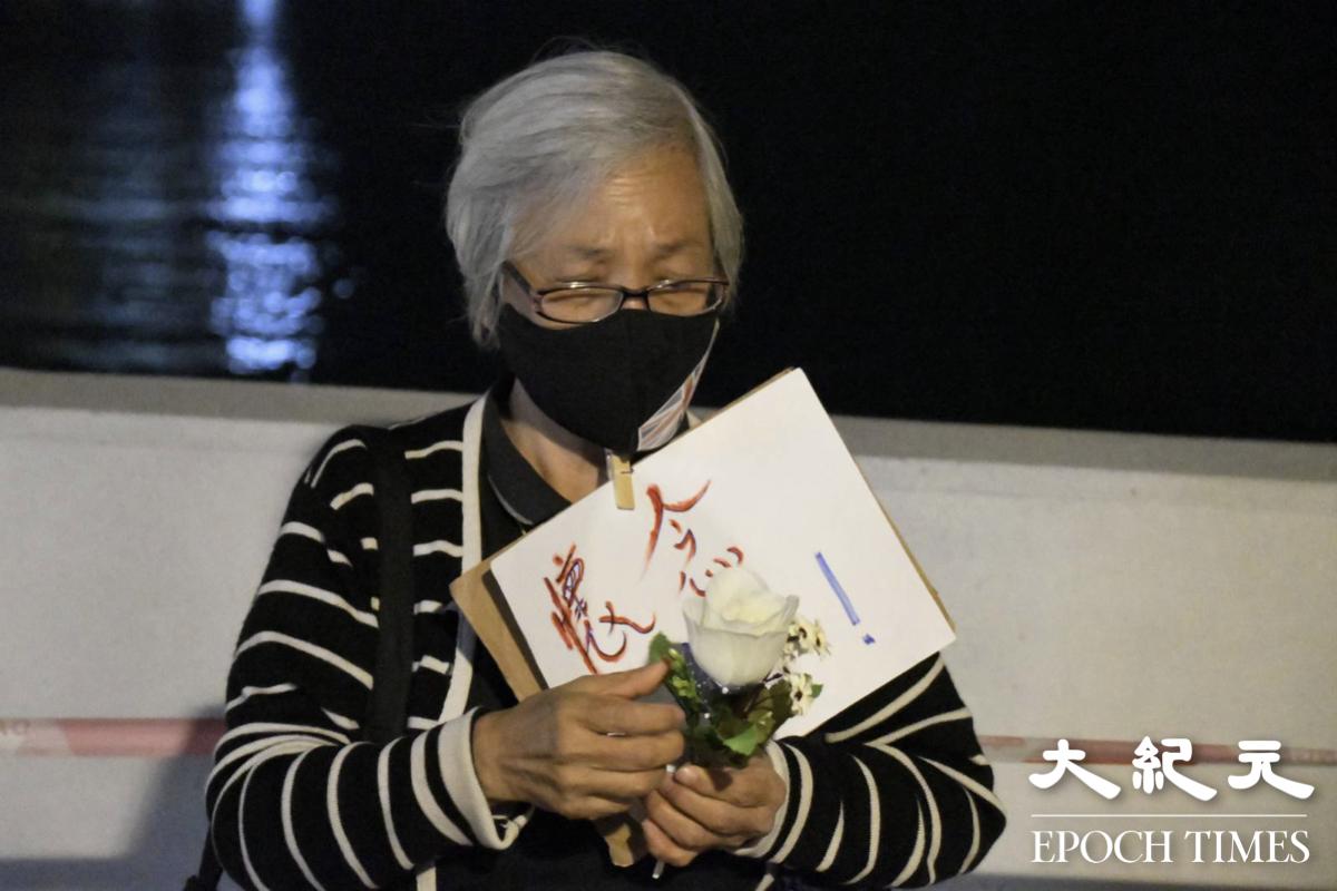 3月8日晚,記者在將軍澳跟王婆婆進行採訪。王婆婆手持白花,想起陳彥霖,只有短短的15年人生,非常感觸。(Big Mack/大紀元)