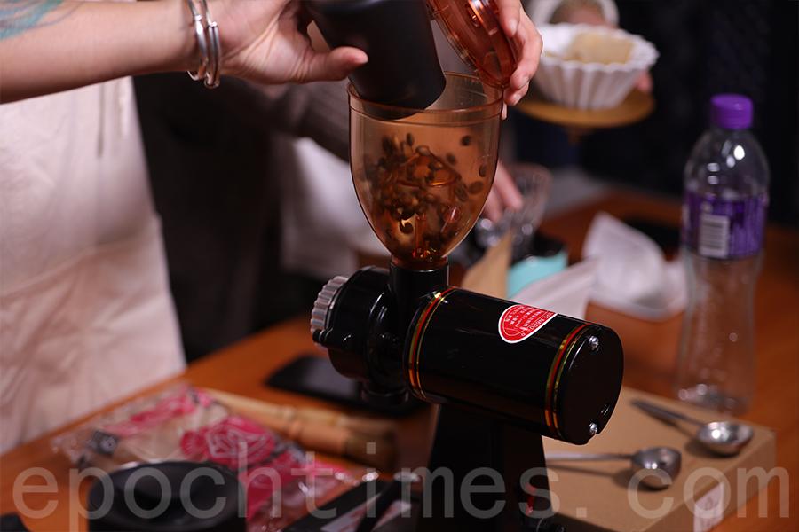 將咖啡豆倒入磨粉機磨成粉。(陳仲明/大紀元)