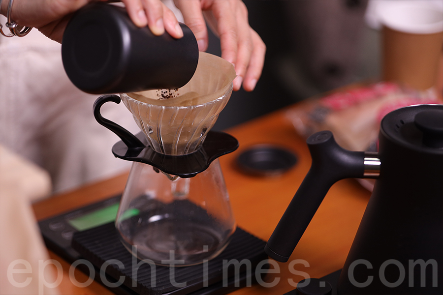 將咖啡粉倒入濾杯。(陳仲明/大紀元)