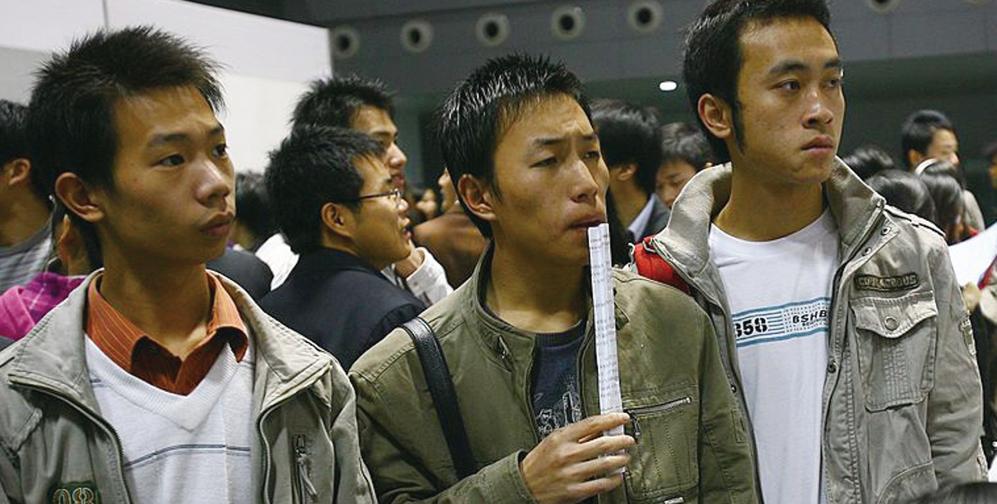 2008年11月28日,中國重慶幾名大學生在一次招聘會上閱讀就業信息。(Getty Images)