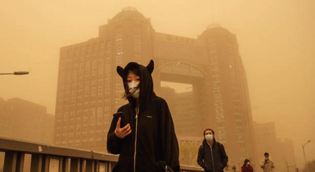 3月15日,北京市民在沙塵暴中行走。(Getty Images)