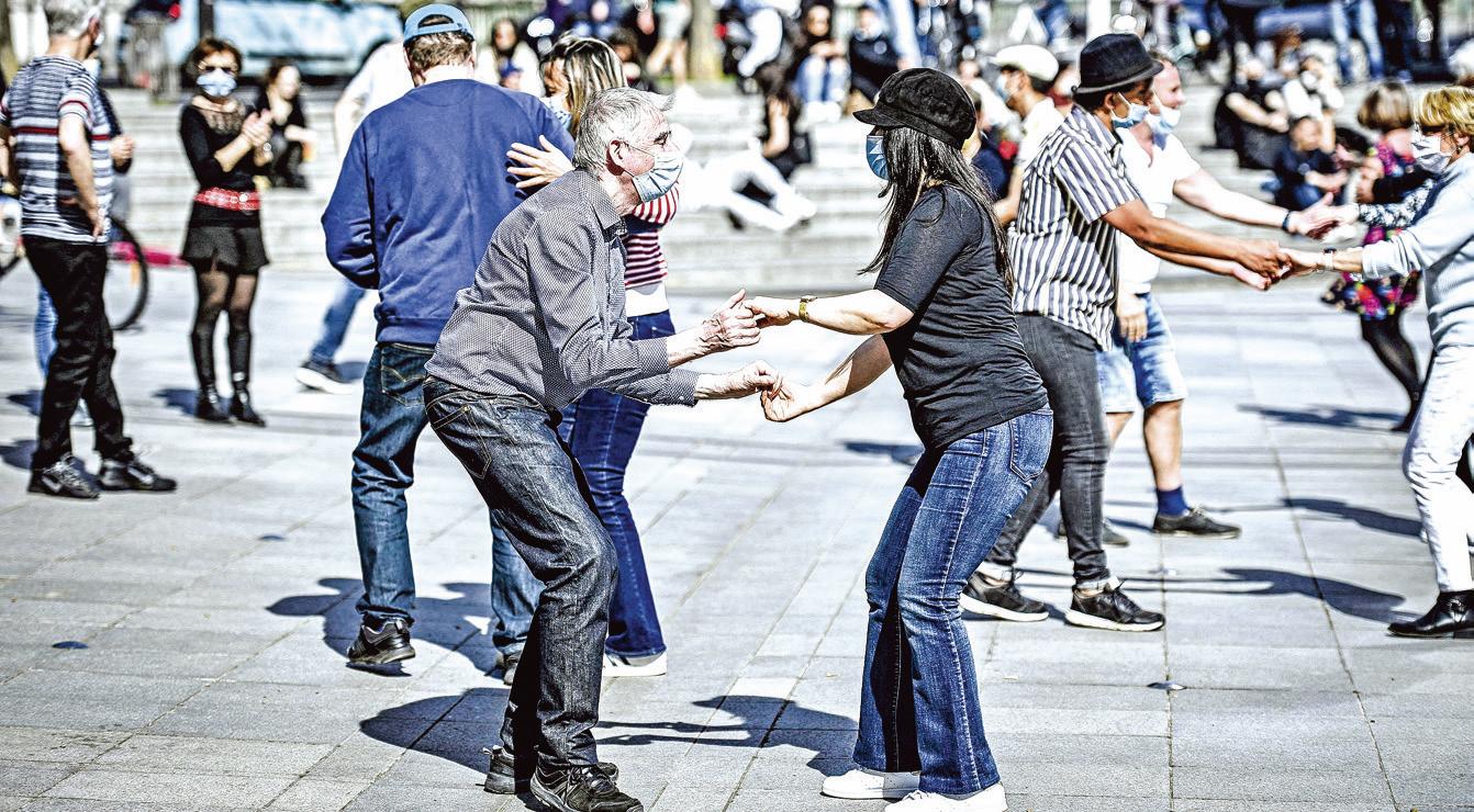 3月28日,法國巴黎為遏制疫情而再度封城的第二個周末,民眾戴著口罩在一個廣場前跳舞。(AFP)
