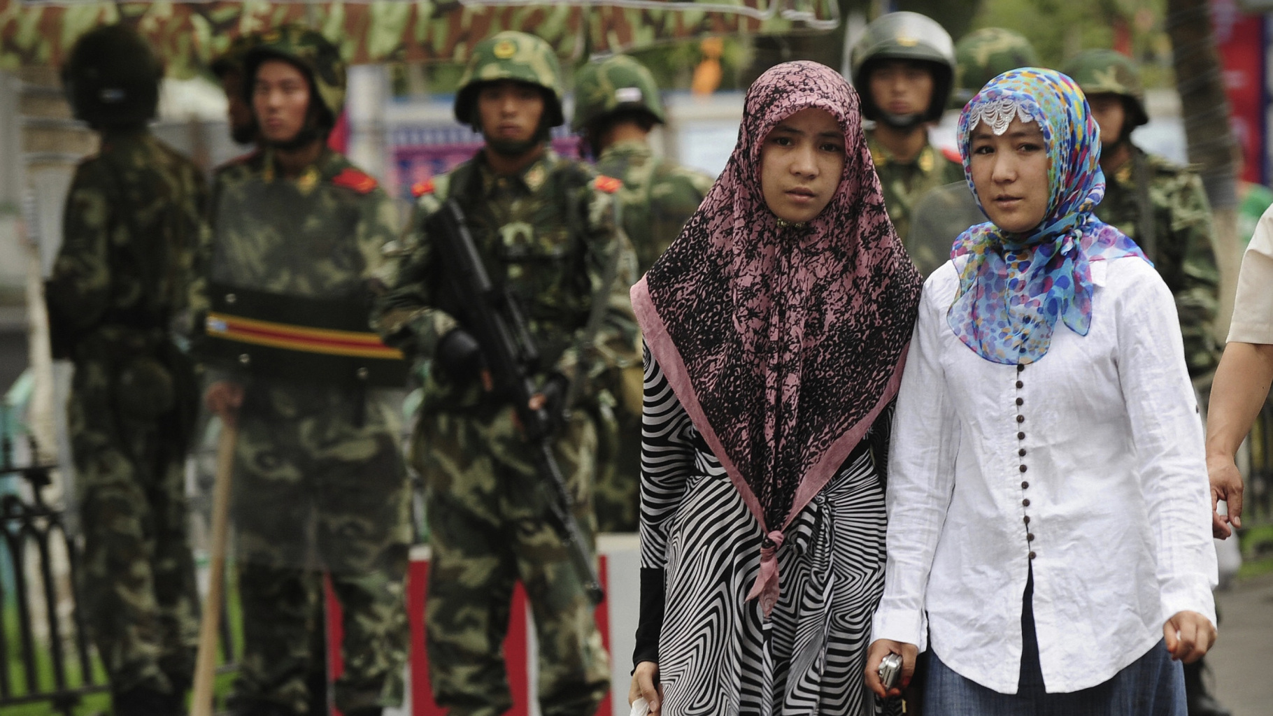 2009年7月14日,兩名新疆婦女路過烏魯木齊的軍警防線。(AFP PHOTO / Peter PARKS/ Getty Images)