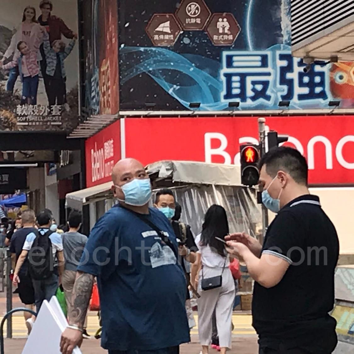 2男1女在被損毀的旺角亞皆老街法輪功真相點旁邊架起污衊法輪功的橫幅,其中一男子是光頭,身上可見有紋身。(周利/大紀元)
