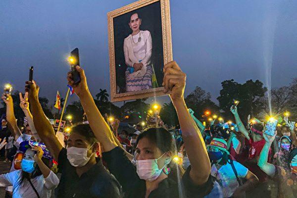 2021年4月4日,居住在泰國清邁的緬甸移民,手持被拘留的平民領袖昂山素姬畫像和手機燈,抗議緬甸的軍事政變。 (DENE-HERN CHEN/AFP/Getty Images)