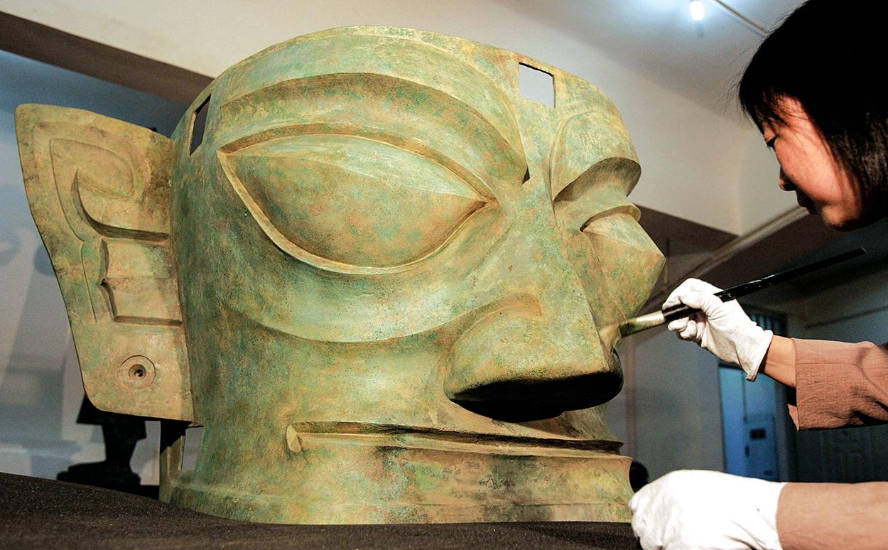 2005年4月13日,考古人員正在復原從三星堆遺址挖掘出來的青銅造像,與中國傳統歷史的印記完全不同。(China Photos/Getty Images)