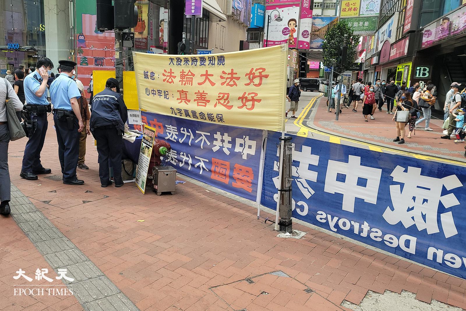 4月8日下午,警方來到銅鑼灣法輪功街站蒐證。(宵龍/大紀元)