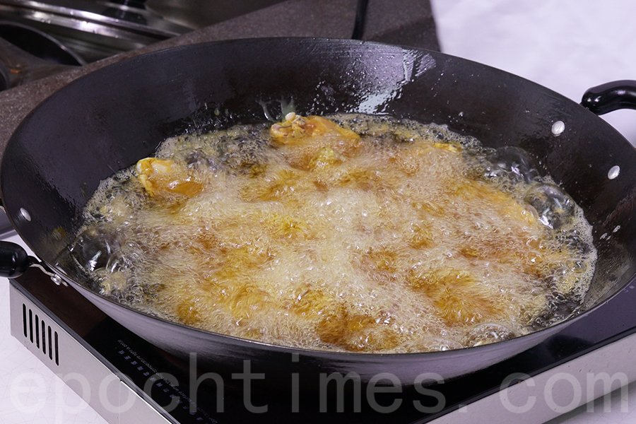 燒熱一鍋生油,將醃好的雞中翼逐件放油鍋內。(陳仲明/大紀元)