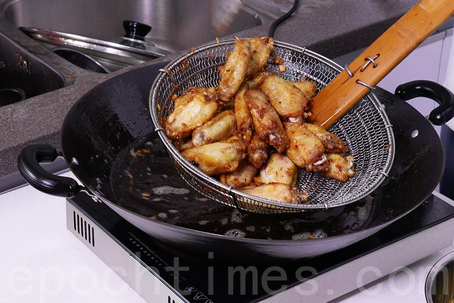 調大火把油再燒熱,將雞中翼回鍋,翻炸至外皮金黃即撈起。(陳仲明/大紀元)