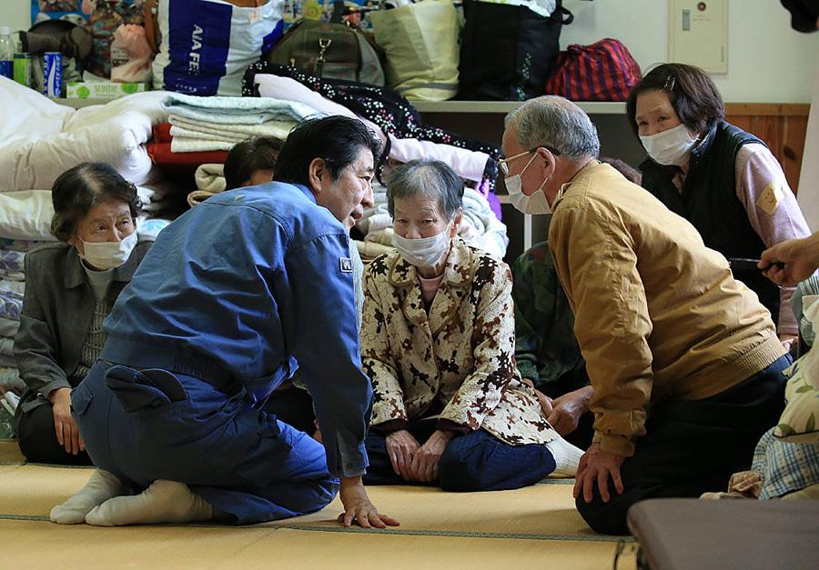 熊本地震後,日本首相安倍晉三到避難所看望災民。(Getty Images)