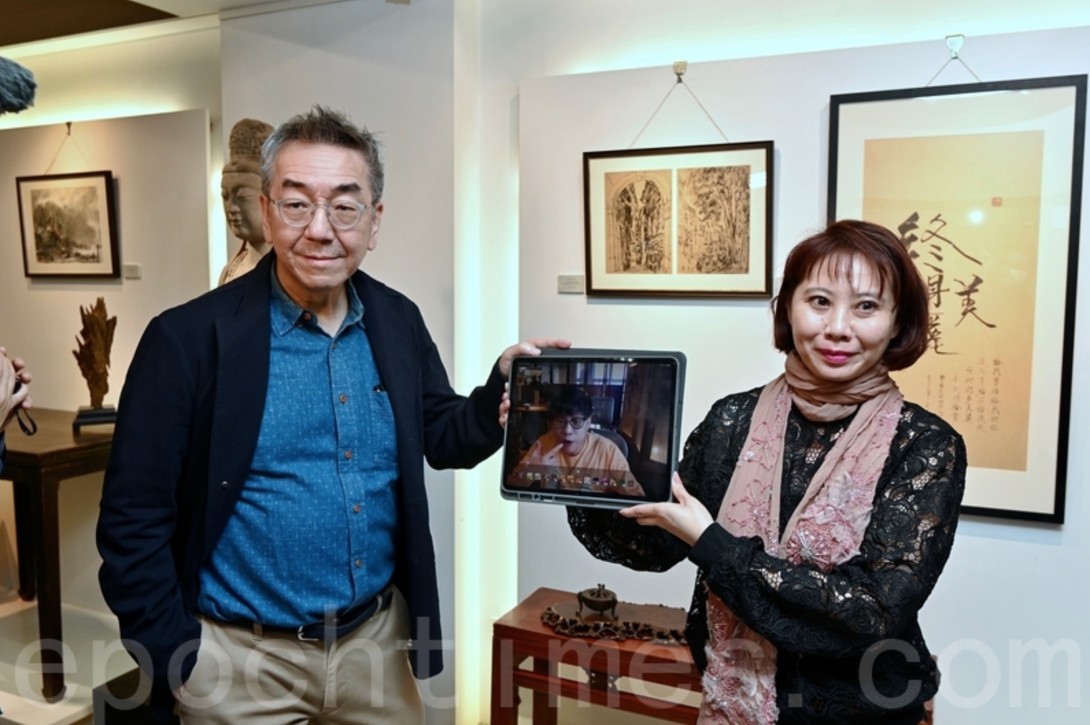 香港作家陶傑(左)與著名作詞人林夕(屏幕中),本月下旬將首次聯合在上環舉辦書畫展。陶傑9日率先到展館導覽,並與身在台灣的林夕透過視像交流暢談。(宋碧龍/大紀元)