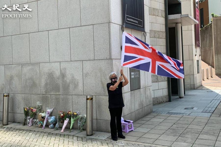 經常參與香港抗爭活動的「王婆婆」王鳳瑤,10日在英國駐香港總領事館外,高舉英國國旗悼念菲臘親王。(自由人快訊提供)