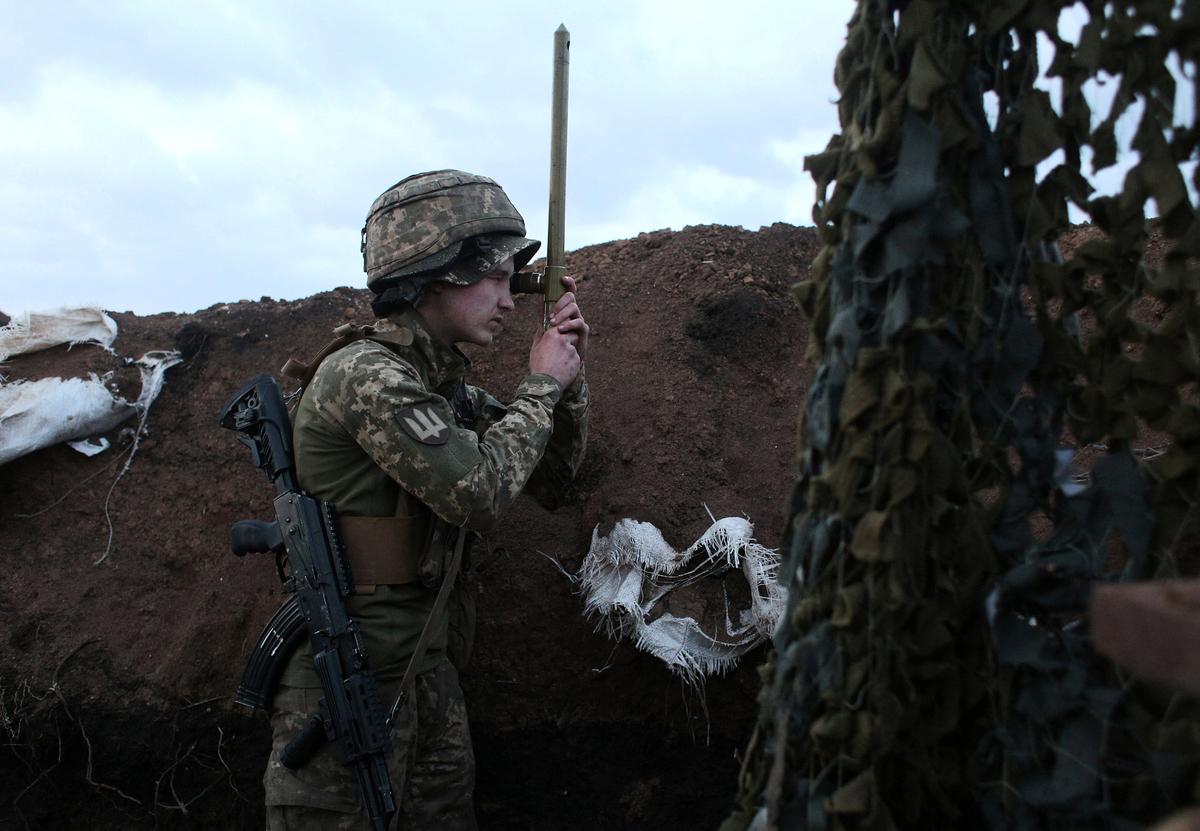 2021年4月8日,前線一名烏克蘭軍人正在使用潛望鏡。(STR/AFP via Getty Images)