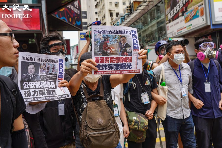 承印香港《大紀元時報》的新時代印刷廠,4月12日再次遭歹徒闖入破壞。時事評論員王岸然讚揚大紀元面對中共不斷打壓,仍屹立不倒,他感言大紀元還存在,香港就還有希望。圖為2020年5月24日銅鑼灣反「港版國安法」遊行中,有市民舉起《大紀元報紙》給警察看。(唐虞/大紀元)