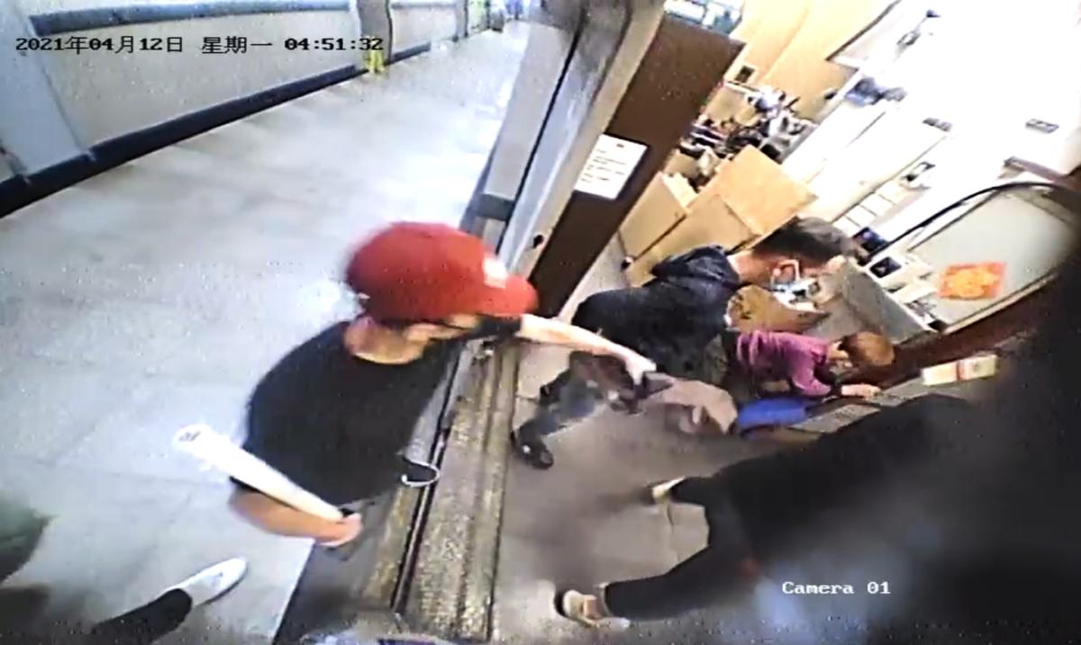 一名戴紅色帽的暴徒手持鎚子衝入印刷廠。(新時代印刷廠閉路電視畫面截圖))