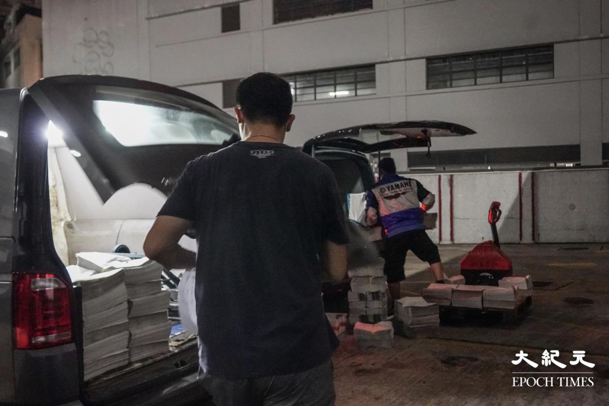 司機阿榮與以往一樣按時到達,幫忙把報紙裝入車內,開車送往各區。(余鋼/大紀元)