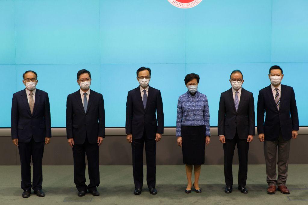 香港公務員事務局長聶德權本周稱,計劃讓香港中高階公務員到中共「掛職」培訓。圖為2020年4月22日香港高管在一個新聞發佈會上,中間兩人分別是聶德權和行政長官林林鄭月娥。(STR / AFP via Getty Images)