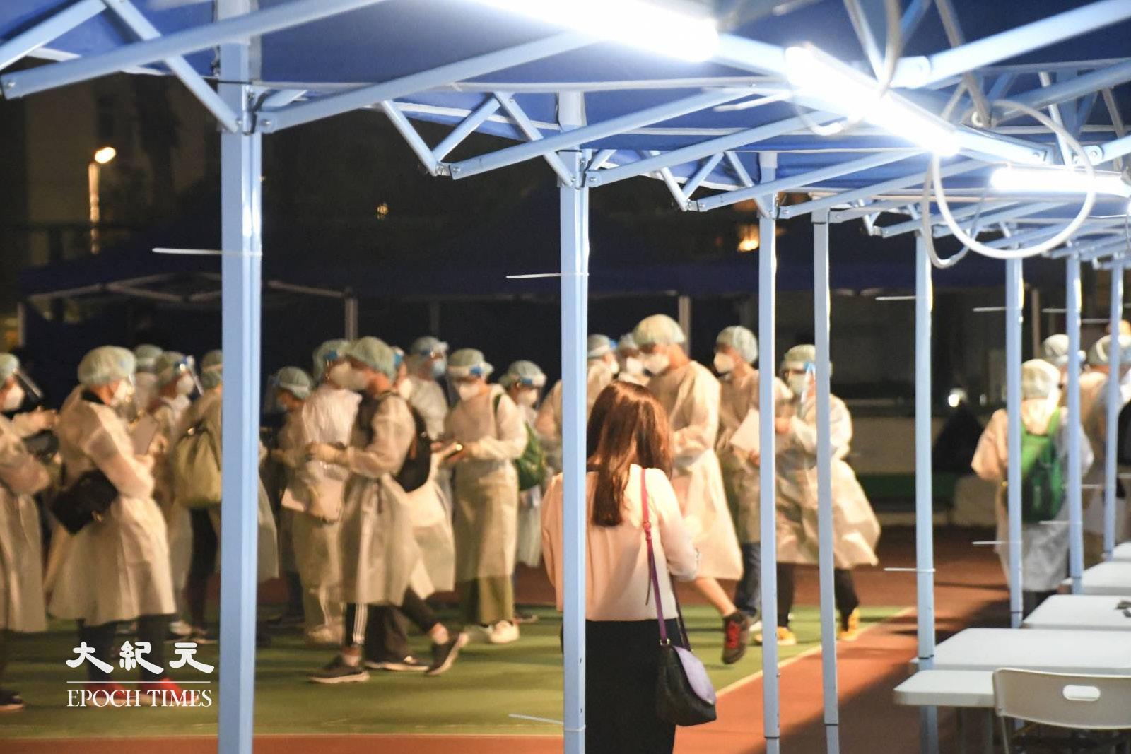 夜晚8時許,數十名穿著保護衣的工作人員在麗城花園二期平台。(麥碧/大紀元)