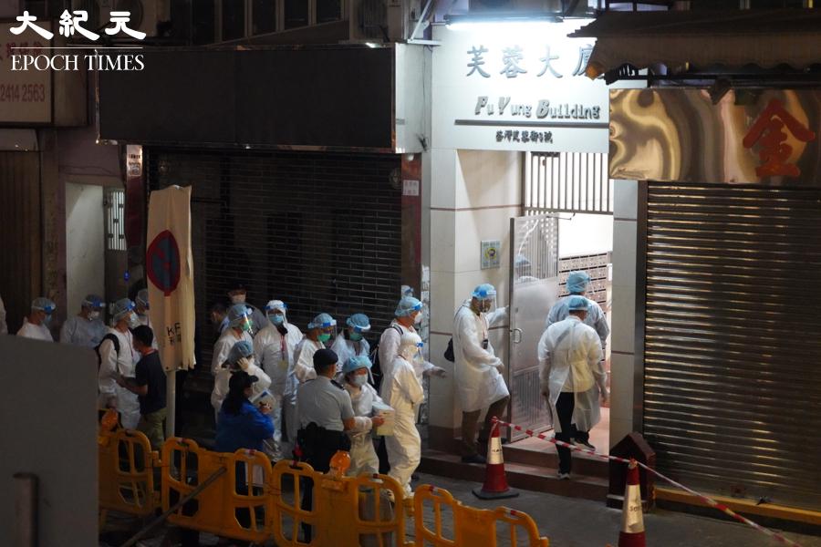 晚上9時20分,身著白色全身防護服的檢測人員進入芙蓉大廈。(余鋼/大紀元)