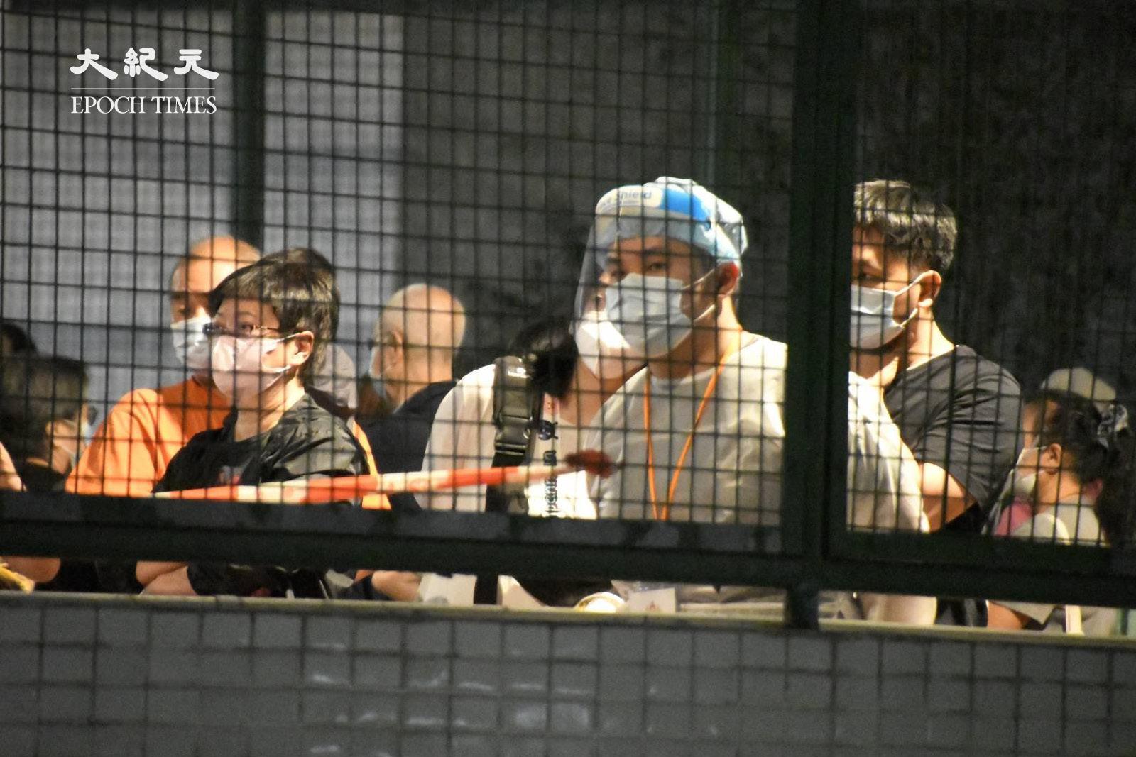 晚上9時許,在麗城花園第二期的平台上,有身穿防護服的工作人員協助居民排隊等候檢測。(麥碧/大紀元)