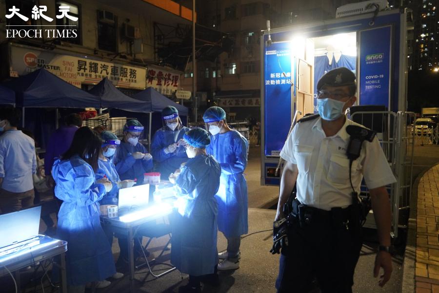 9時15分,在荃灣芙蓉街,醫護人員在準備檢測試劑,有警員在附近巡視。(余鋼/大紀元)