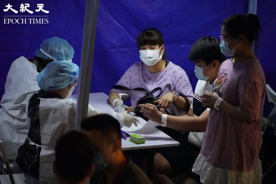近10時,芙蓉大廈住戶在藍色帳篷內接受檢測。(余鋼/大紀元)