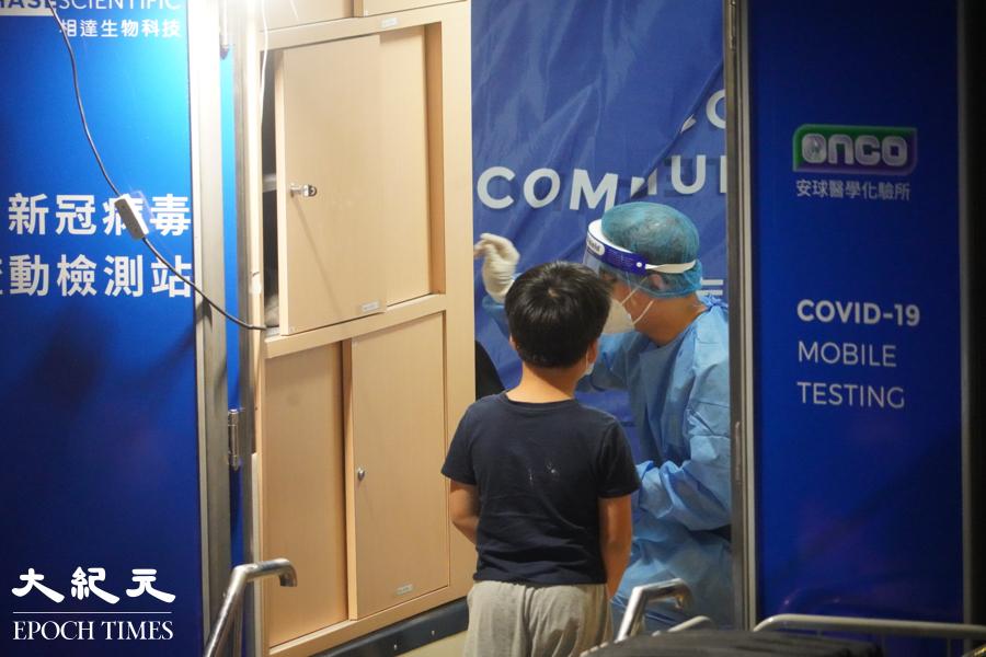 近10時,在芙蓉大廈居住的小朋友在流動車內等候檢測。(余鋼/大紀元)