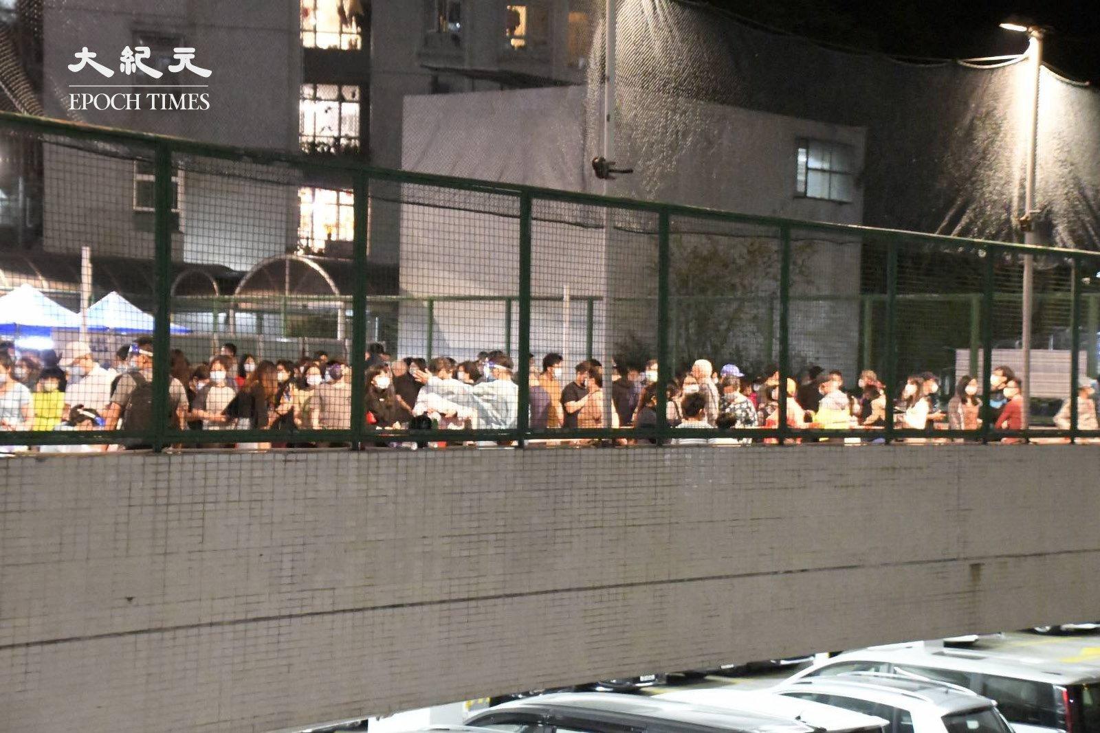 夜晚10時許,麗城花園第二期第4座的居民排隊檢測。(麥碧/大紀元)