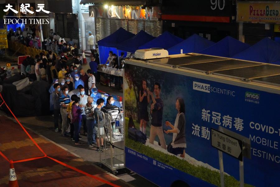 晚上10時許,芙蓉大廈等待檢測的住戶排成長龍,隊伍排至街尾。(余鋼/大紀元)