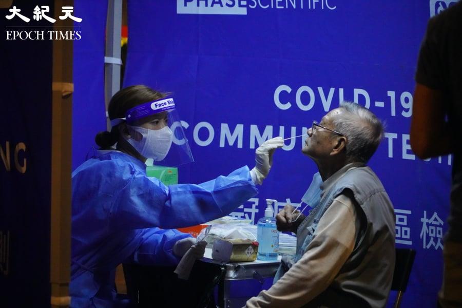 晚上10時許,芙蓉大廈居民在接受病毒檢測。(余鋼/大紀元)
