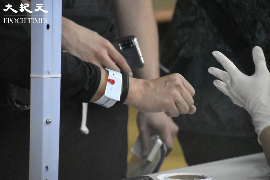 麗城花園二期,居民於檢測後被扣上手帶,工作人員吩咐 : 直至政府宣布解封之前,請不要將手帶剪下。(麥碧/大紀元)