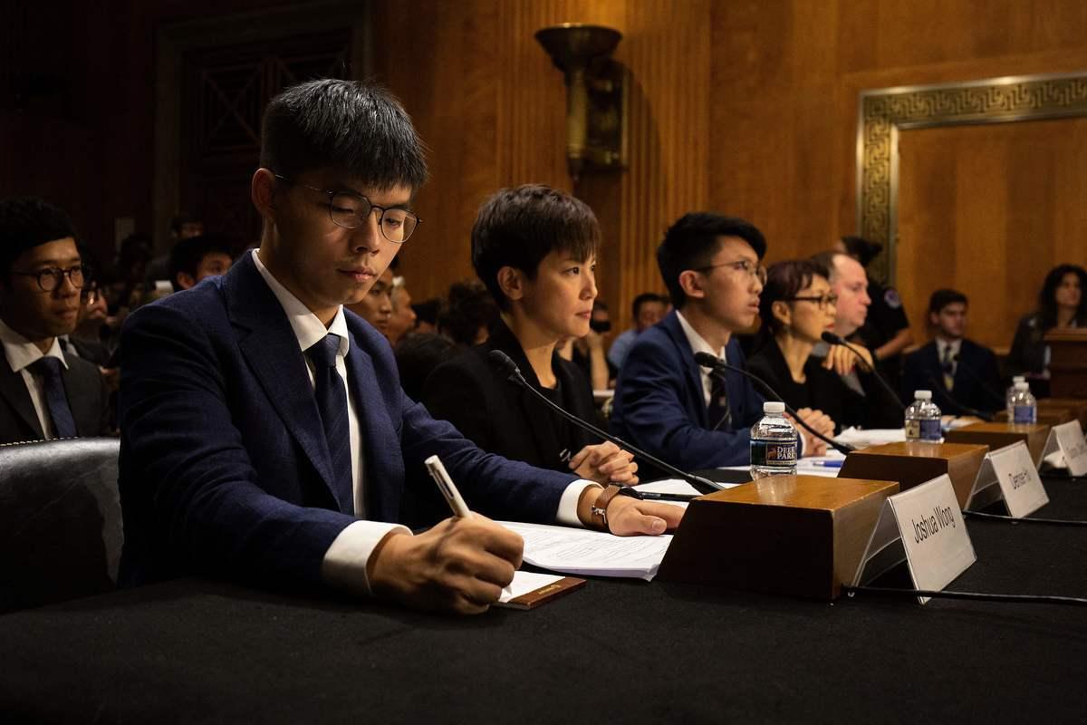 HKFP查獲資料發現,黃之鋒(左)、何韻詩(中)和張崑陽(右)抵達美國進行《香港人權與民主法案》遊說前,港府花錢委託「中間人」遊說美方反對法案。(ALASTAIR PIKE/AFP via Getty Images)