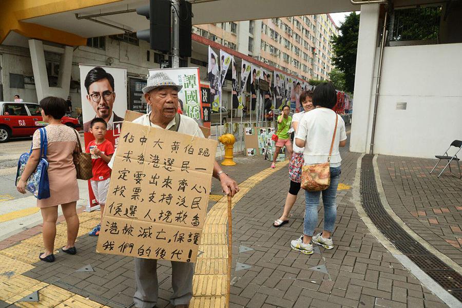 92歲黃伯今早在石硤尾呼籲全港市民出來投票,支持民主黨,一起抗拒中共入侵,不要讓民建聯當選,否則香港民眾將家無寧日。(宋祥龍/大紀元)
